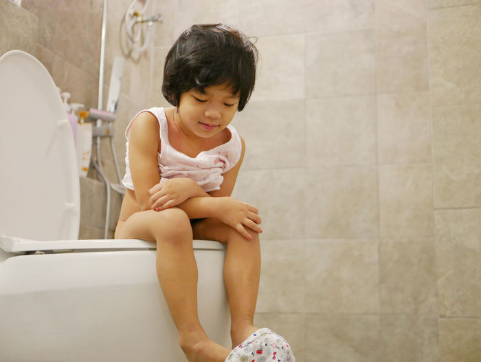 Little Asian baby girl, 38 months old, feeling proud being able to go, get on, and use adult size toilet bow by herself successfully for the first time Baby Girl Asian  Sitting Training Potty Toilet Bowl Adult Size Child Kid Toddler  Successfully Success Happy Proud By Herself Able To Bathroom Restroom House Home Routine Morning Use
