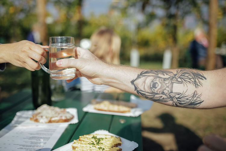 Cropped Hands Of People Holding Drink At Backyard