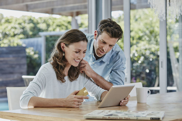 Rear view of man and woman using phone while sitting on table