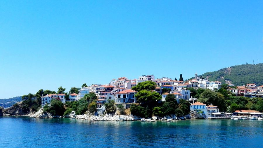 Houses By Sea Against Clear Blue Sky