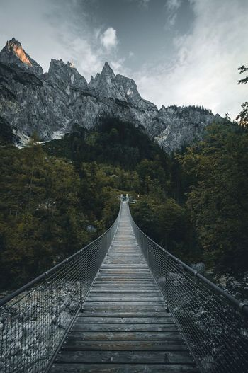 Footbridge leading towards mountains against sky