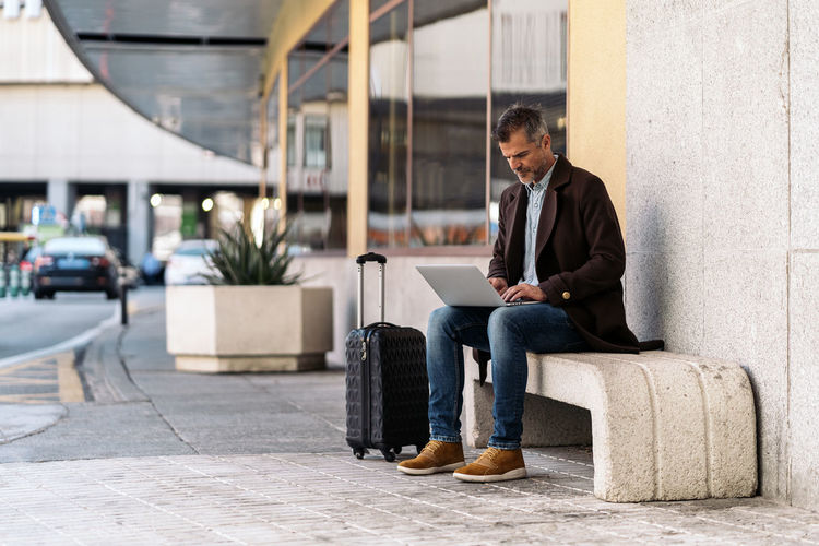Full length of man using mobile phone while sitting on seat