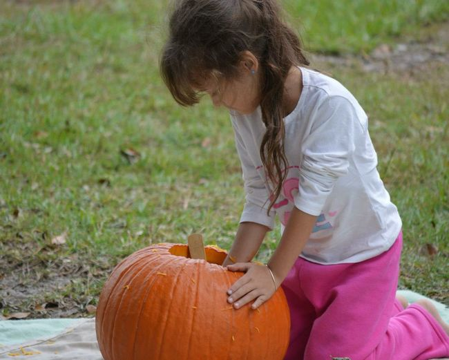 Girl carving pumpkin while kneeling on grassy field