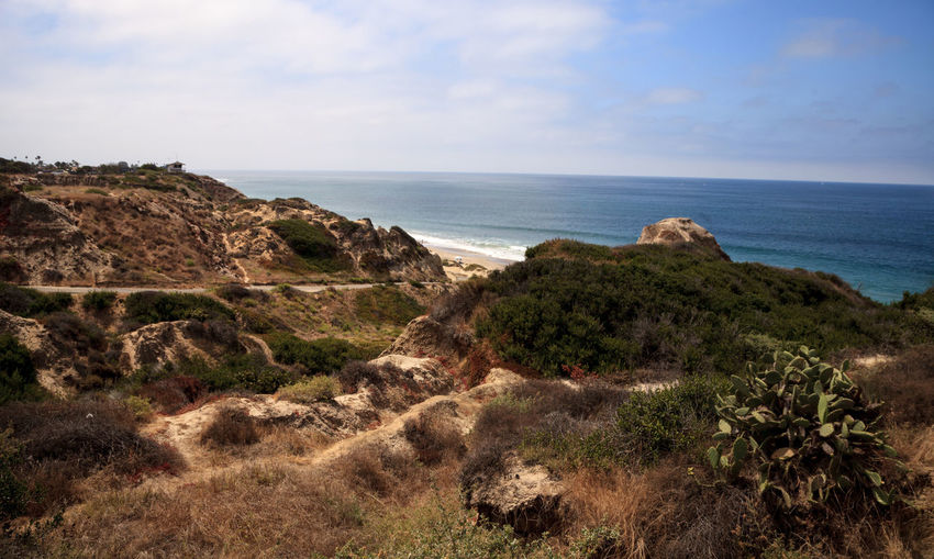 Scenic view of cliff and sea against sky