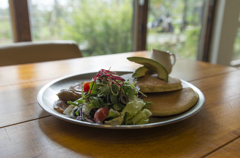 Close-up of pancakes with salad served in plate on wooden table