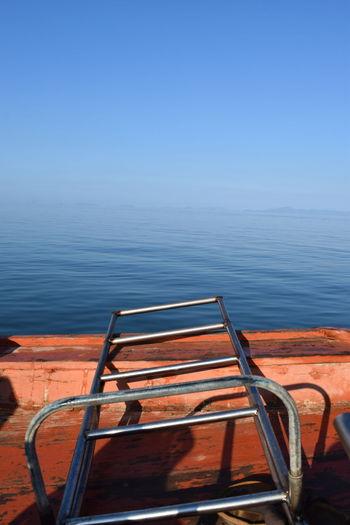 Metallic Ladder On Boat In Sea Against Clear Blue Sky