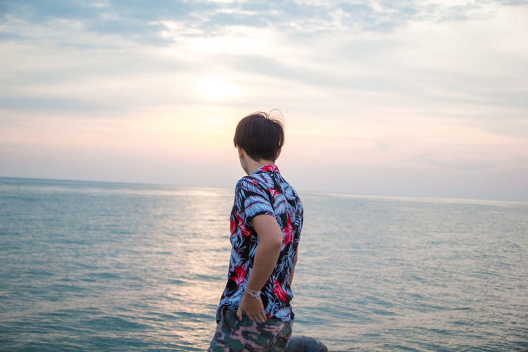 Boy standing in sea against sky during sunset
