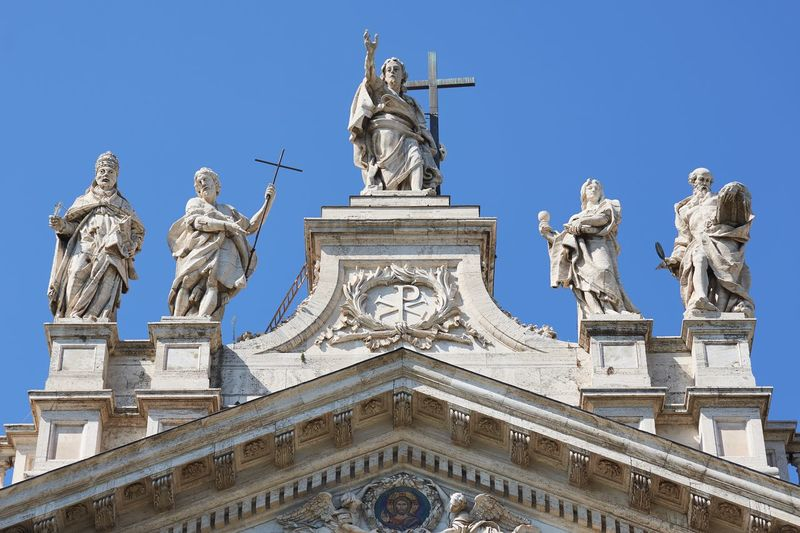 Low angle view of statues on church against sky