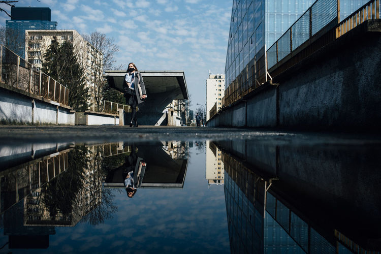Reflection of man standing on puddle against buildings