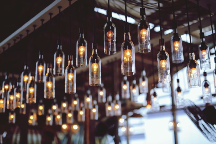 An Urban Light covered with bottle with beauty arrangement. Illuminated Lighting Equipment Hanging No People Indoors  Decoration Selective Focus In A Row Glowing Built Structure Large Group Of Objects Light Belief Group Night Restaurant Glass - Material