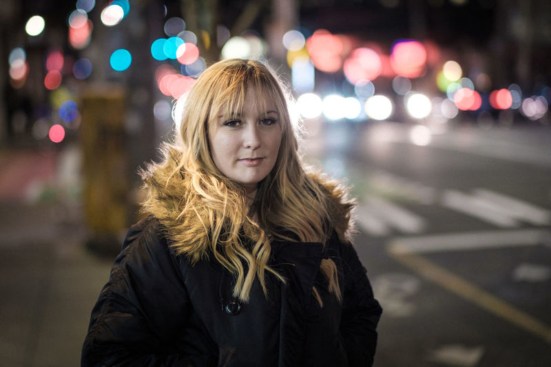 Portrait of young woman standing on sidewalk in illuminated city