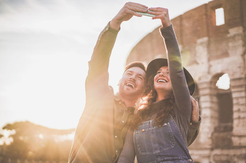 Cheerful couple taking selfie while standing outdoors