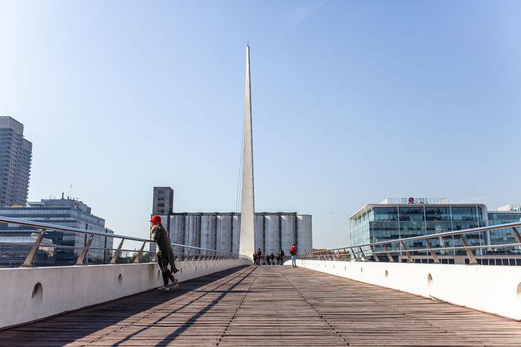 Footpath leading towards buildings against clear sky