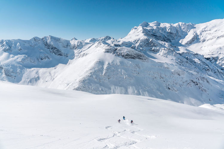 Group of people skiing in fresh powder snow in vast alpine landscape, gastein, austria.