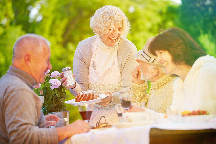 Friends Enjoying At Dining Table In Garden
