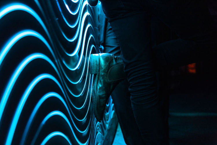 Midsection of man standing against illuminated wall at night