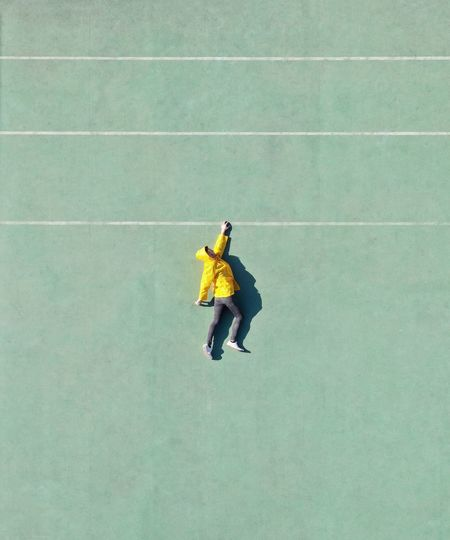 Directly above shot of man lying on playing field
