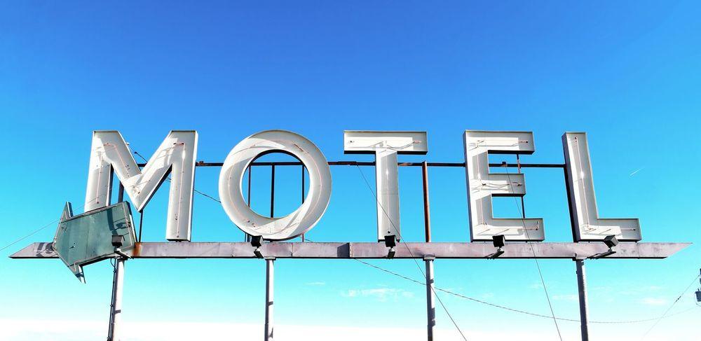 Information Medium No People Sky Business Accomodation Hotel Motel Sign Sign Arrow Arrow Symbol Text Words Signage Inn Motel Motels Accomodations Service Industry Sleep Tired Sleepy Blue Sky Backgrounds Old Sign