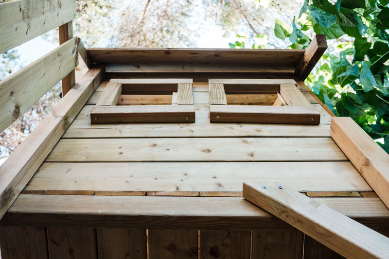 Low angle view of wooden bench on building