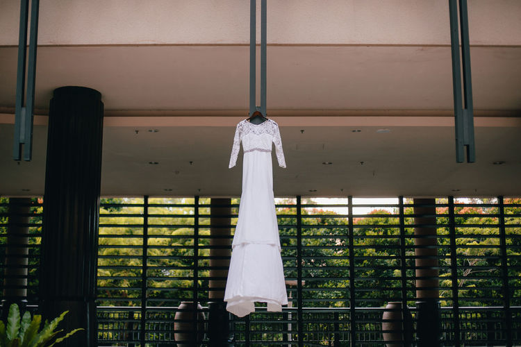 Low angle view of wedding dress hanging on building