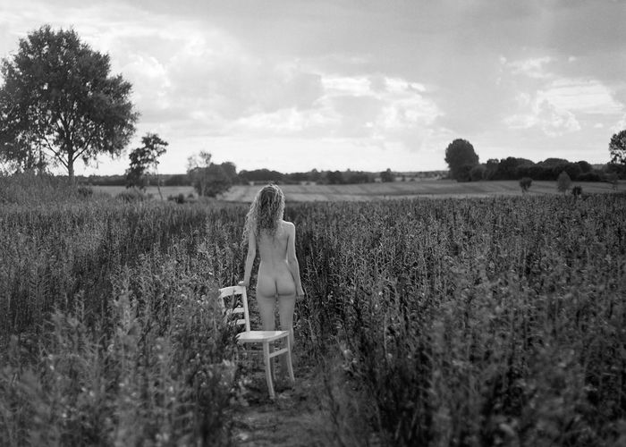Rear View Of Naked Woman With Chair Standing Amidst Plants On Field