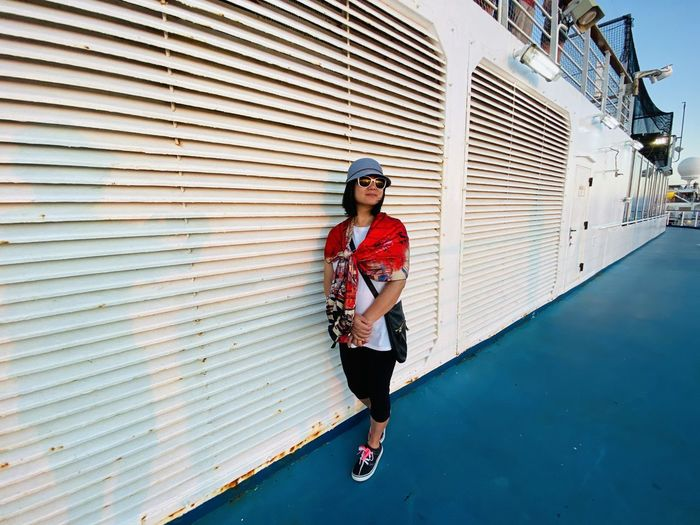 Woman wearing sunglasses standing in ship