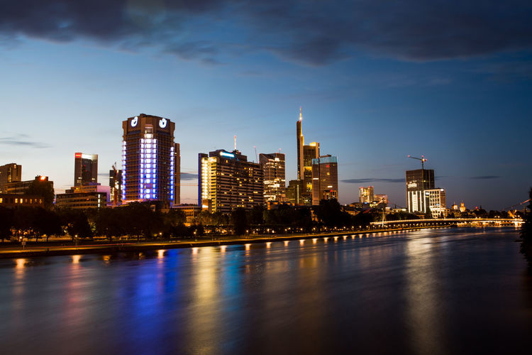 Illuminated buildings by river against sky in city in frankfurt, germany