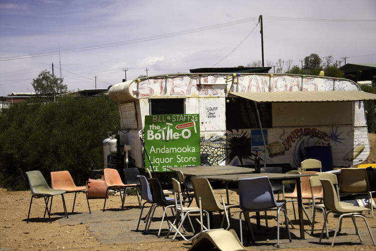 Empty chairs and tables by food truck