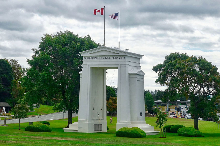 The Peace Arc at the westernmost border between Canada and the USA. Peace Arch Trees USA Architecture Border Building Exterior Built Structure Canada Clouds Day Flags Grass Lawn Memorial No People Outdoors Sky Westernmost