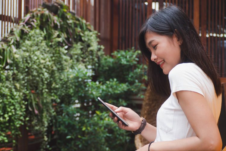 Side View Of Woman Using Phone While Standing Against Plants