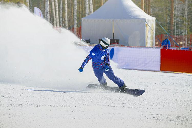 Full length of man skateboarding on snowy field during winter