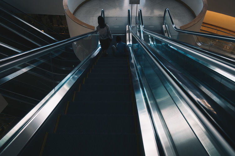 Steps And Staircases Staircase Railing Architecture Escalator Convenience Real People Indoors  Technology The Way Forward Direction Modern Low Angle View Lifestyles Built Structure Moving Up One Person Motion on the move Moving Walkway