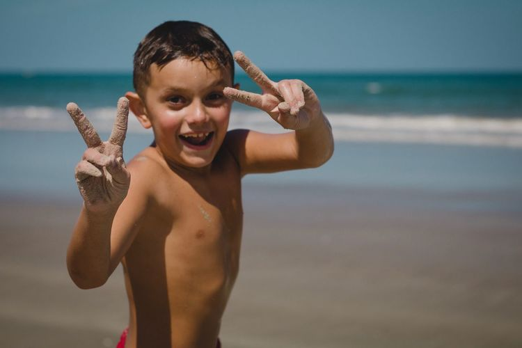 Portrait of happy shirtless boy showing peace sign while standing at beach