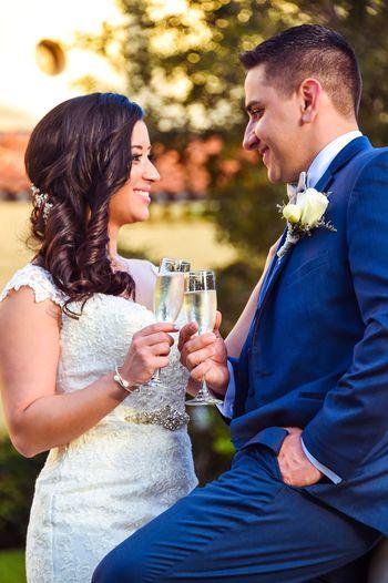 Smiling bridal couple toasting champagne flutes