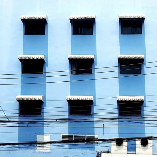 Low angle view of electricity cables against blue building