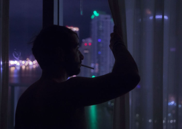 Side view of man looking through window night