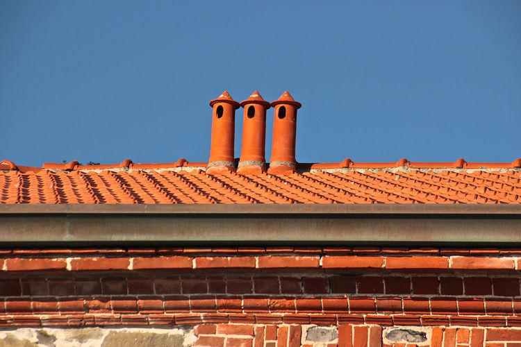 Three chimney pots Built Structure Architecture Building Exterior Blue Clear Sky Sky Low Angle View Roof Building No People Day Nature Sunlight Roof Tile Outdoors Orange Color History The Past Window Copy Space Three Objects Chimney Pots Shingles Roof