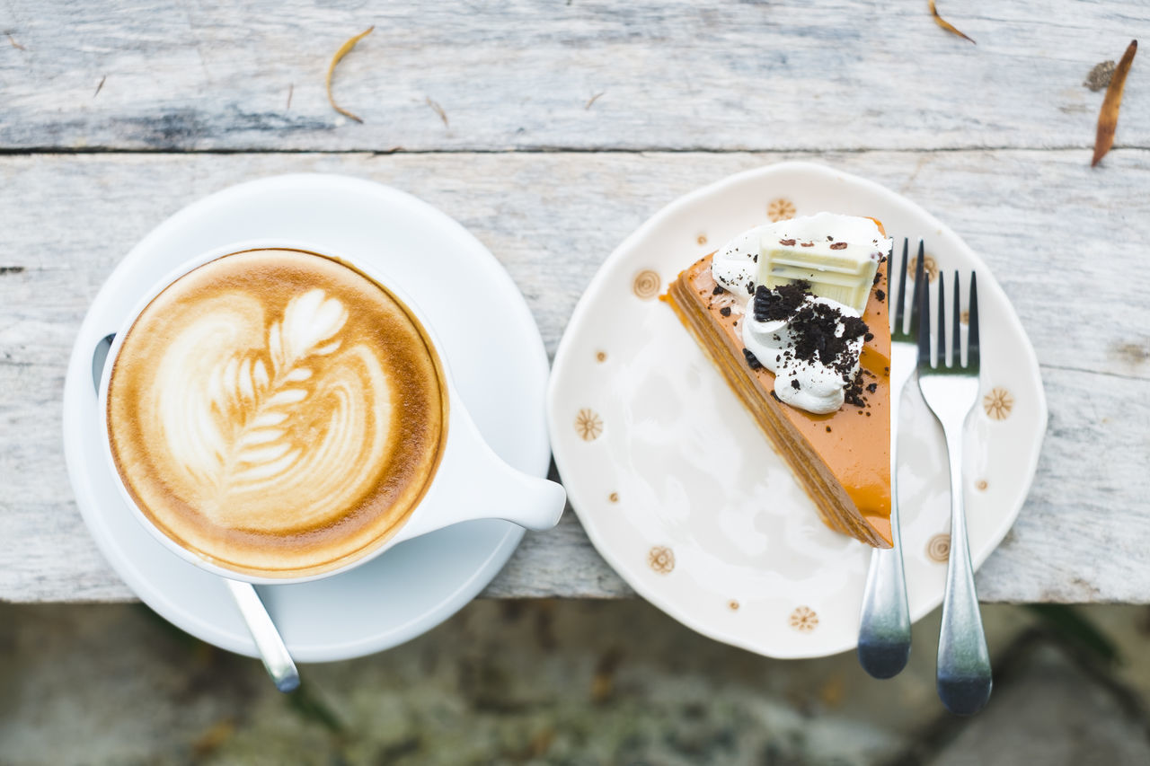 High Angle View Of Cappuccino And Cake In Plates On Table