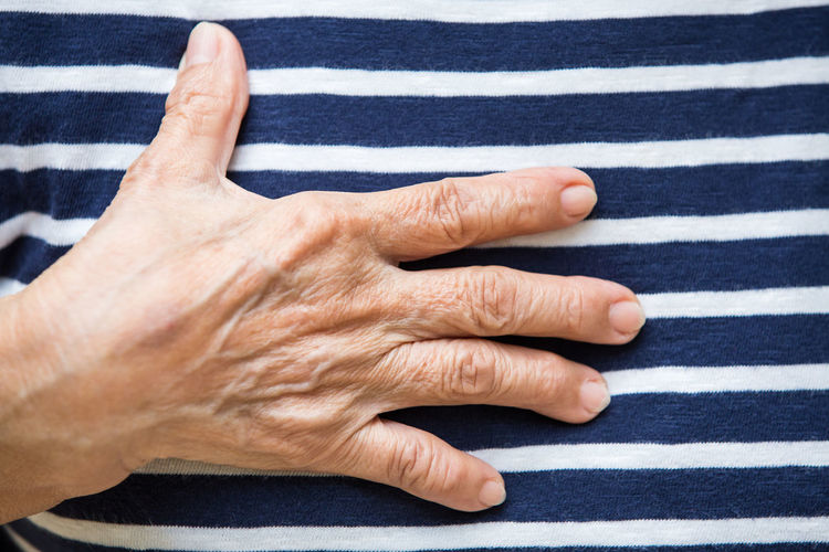 Senior woman's hands action on striped T shirt background Hands Touch Action Adult Close Up Close-up Concept Finger Grandmother Hand Holding Human Body Part Human Hand Lifestyles Old People Selective Focus Senior Adult Senior Women Skin Striped Symbol T Shirt Trendy Wrinkled Skin