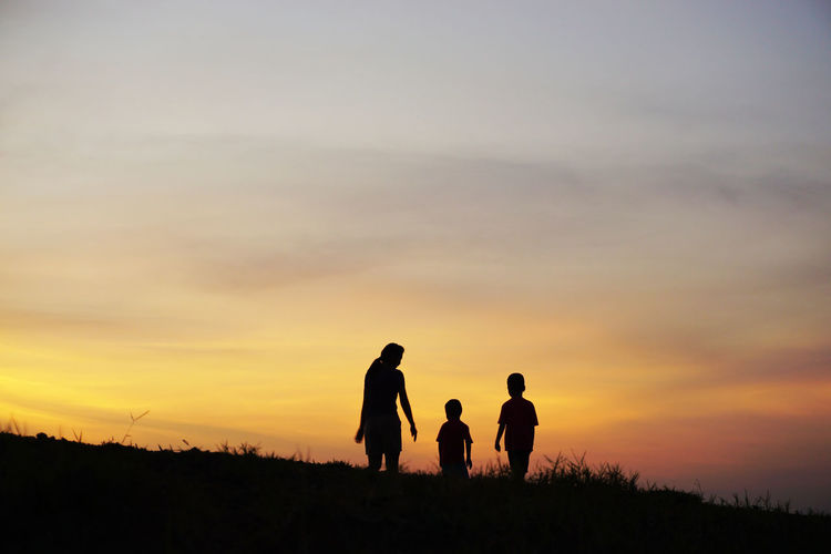 Silhouette Mother Walking With Sons On Field Against Orange Sky