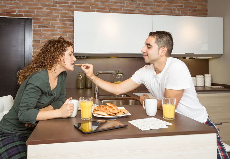 Happy young man feeding her girlfriend with a cookie in weekend home breakfast Family Fruit Girlfriend Thirties Relaxing Husband Boyfriend 30s Wife Relationship Adult Lifestyle Interior Love Cup Caucasian Healthy Two Coffee Orange Girl Juice Meal Drink Together Young Woman Kitchen Man Indoors  Food Morning Technology Newspaper Digital Tablet Eating Feeding  Smiling Cheerful Happiness Smile Happy Male Home People Female Couple Breakfast