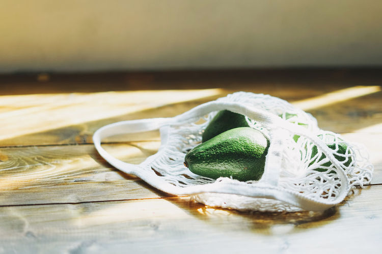 Close-up of avocados with mesh bag on table