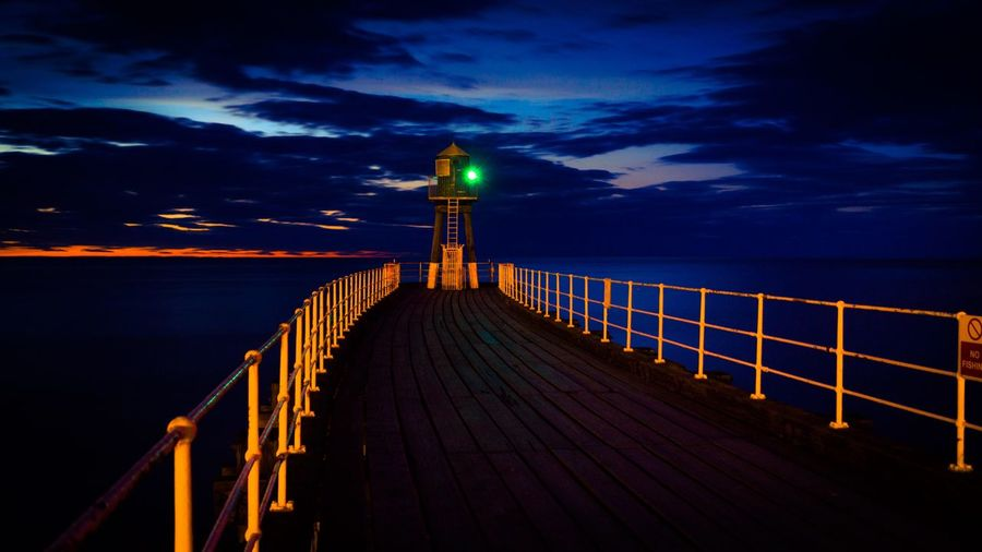 Lighthouse And Pier On Sea Against Sky During Sunset At Yorkshire