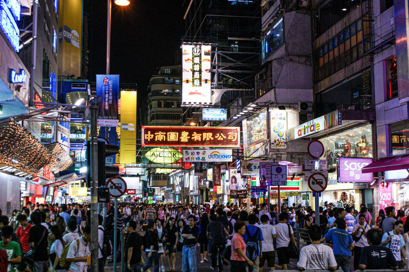Crowd on city street by buildings at night
