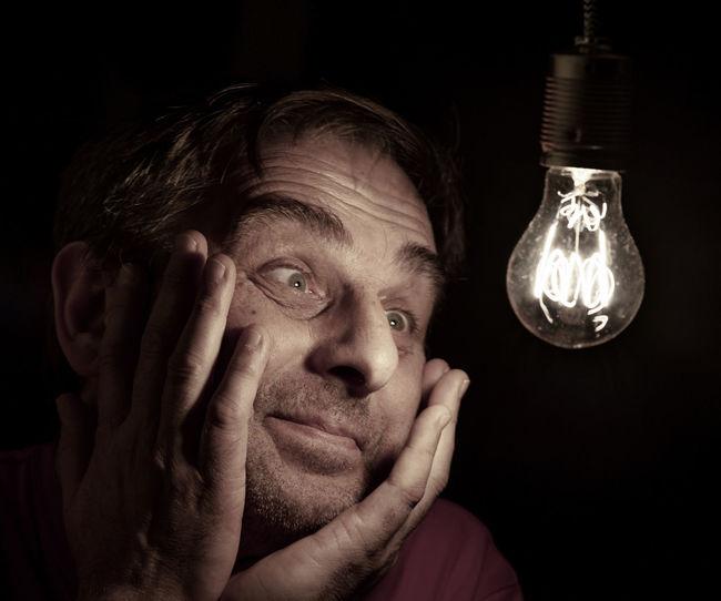 Close-Up Of Smiling Mature Man Looking At Illuminated Light Bulb In Darkroom