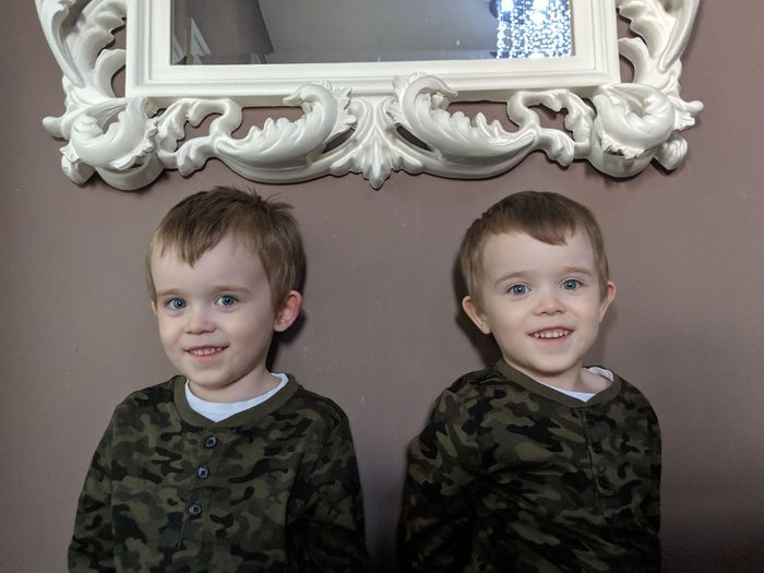 Portrait of smiling brothers standing against wall at home