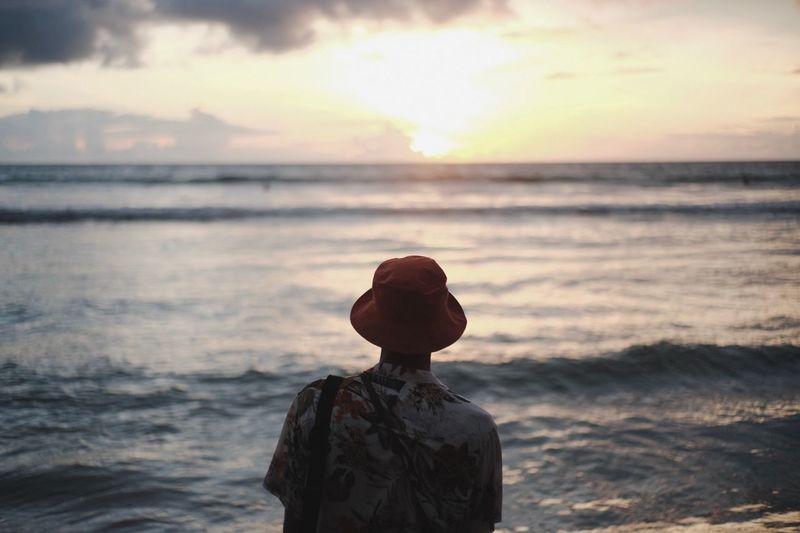 Rear view of man wearing hat while looking at sea