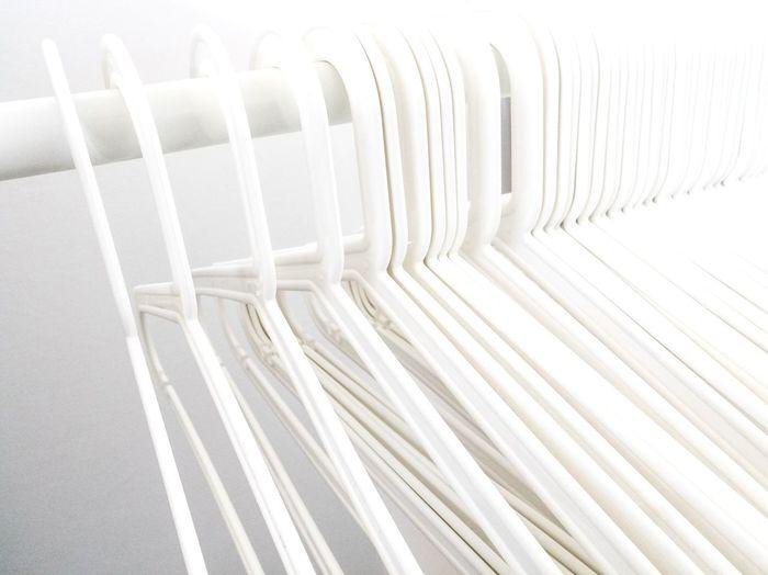 Close-up of white coathangers on rod