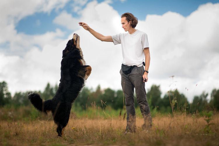 Man training dog on grassy land against cloudy sky