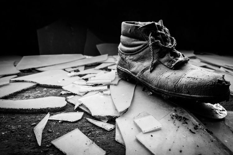 Close-up of shoe on broken glass